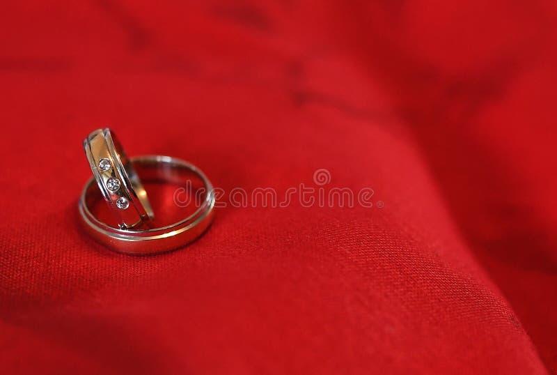 Paires d'anneaux les épousant d'or sur le velours rouge images stock
