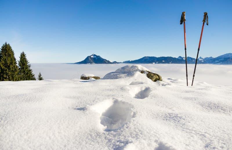 Paires d'augmenter des bâtons et des empreintes de pas dans la neige Activité sportive dans le paysage d'hiver de montagnes Allga photographie stock
