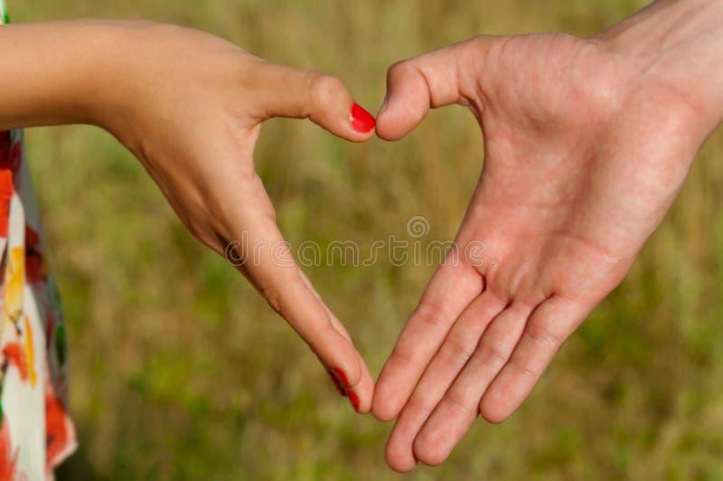 Paires d'en forme de coeur pliées par mains photographie stock libre de droits