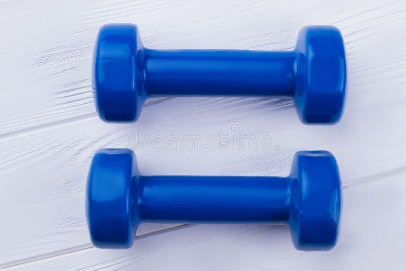 Paires d'haltères bleues sur le fond en bois images stock