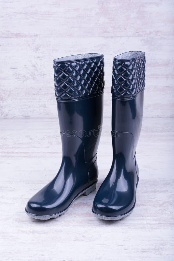 Paires de bottes en caoutchouc bleues sur le fond en bois blanc images stock