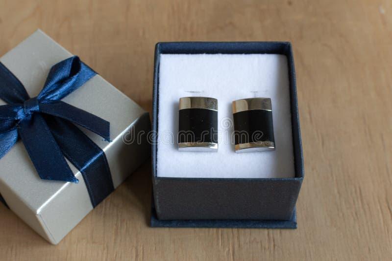 Paires de boutons de manchette dans un boîte-cadeau sur le fond en bois images libres de droits