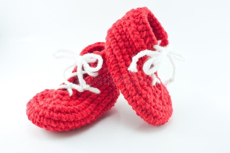 Paires de butins rouges tricotés et lumineux de bébé image libre de droits