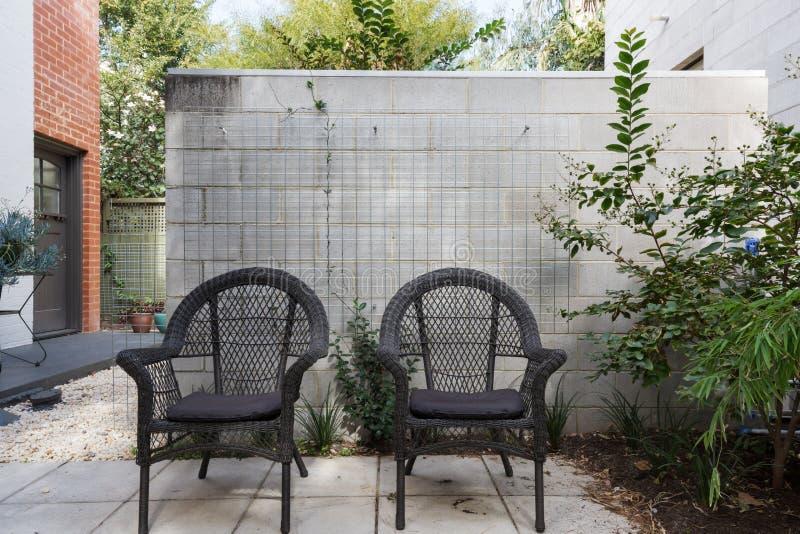 Paires de chaises extérieures de canne noire dans la cour moderne photographie stock libre de droits