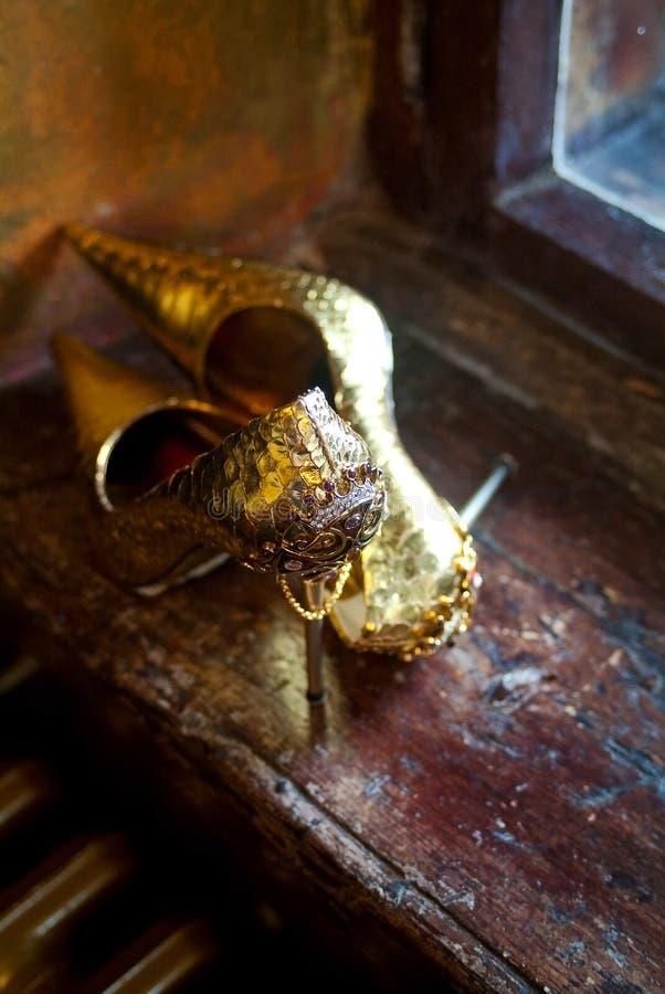 Paires de chaussures d'or jeweled dans l'intérieur antique images stock
