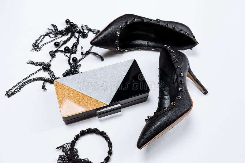 Paires de chaussures noires d?cor?es des accents en m?tal, des bijoux avec la dentelle et les perles noires et d'un embrayage tri image libre de droits