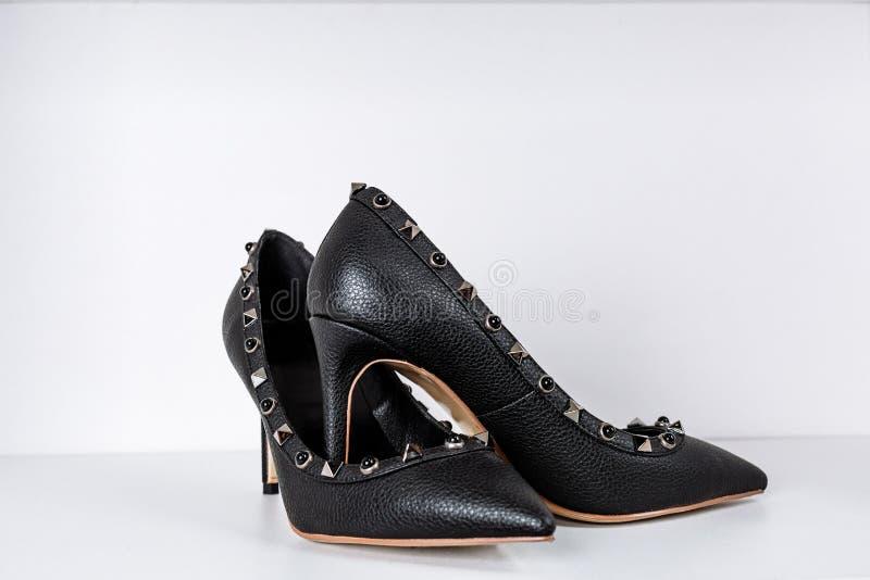 Paires de chaussures ? talons hauts noires avec les orteils aigus, d?cor?es des insertions en m?tal contre une ?tag?re dans le ma image stock