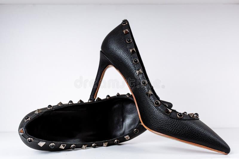Paires de chaussures ? talons hauts noires avec les orteils aigus, d?cor?es des insertions en m?tal contre une ?tag?re dans le ma photographie stock