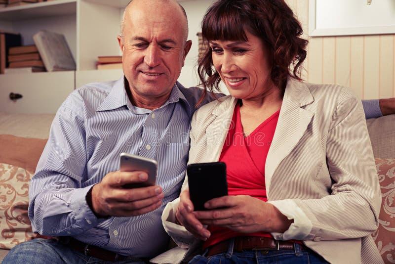 Paires de deux joyeux conjoints jouant avec des dispositifs photos libres de droits