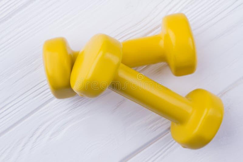 Paires de dumbells jaunes sur le fond en bois blanc photos stock