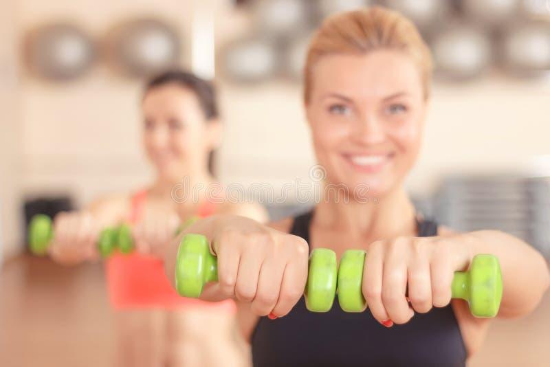 Paires de femmes faisant la forme physique de poids image stock