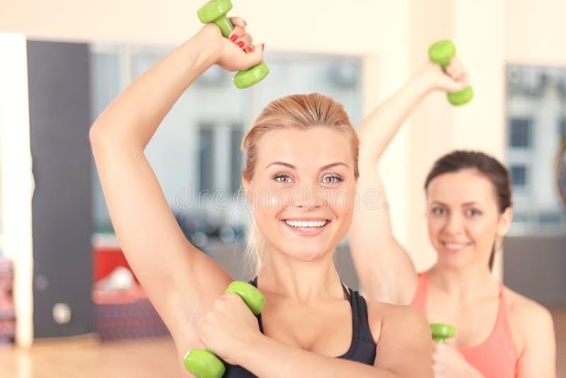 Paires de femmes faisant la forme physique de poids photographie stock libre de droits