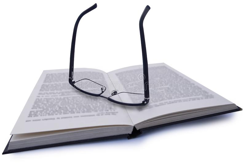 Paires de lunettes, se reposant sur le livre avec le texte trouble avec l'écriture claire par la lentille image libre de droits