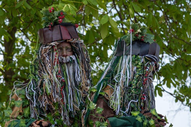 Paires de lutins d'arbre avec de longues barbes et houx se tenant sous l'arbre de marron d'Inde photographie stock libre de droits