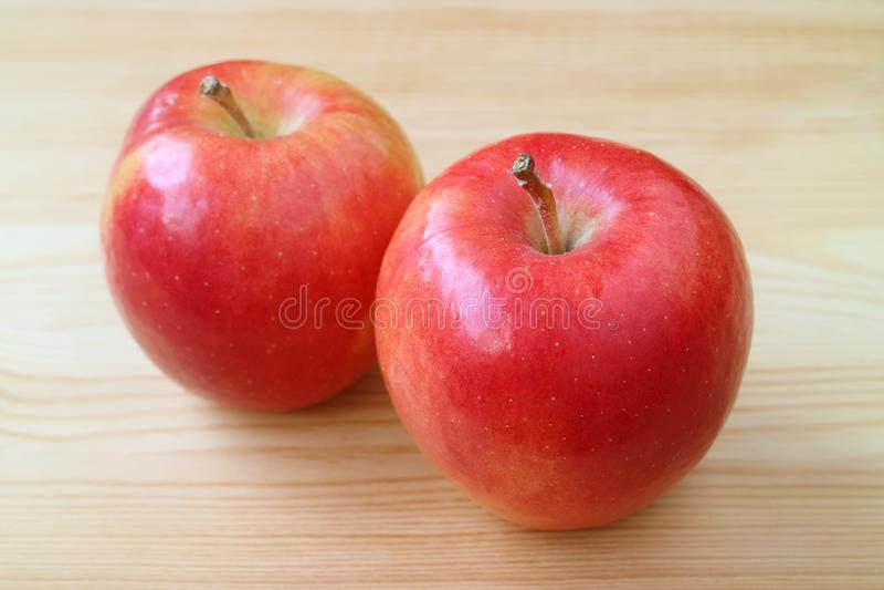 Paires de pommes rouges vibrantes fraîches sur la table en bois brun clair image stock