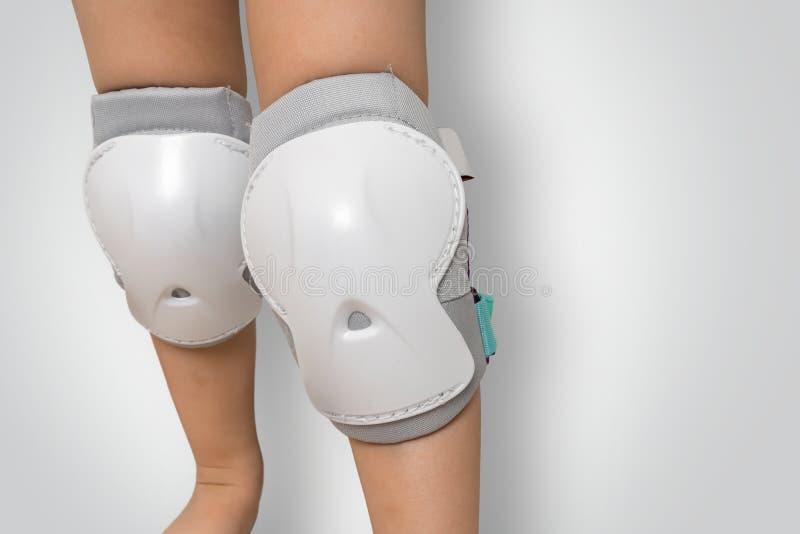 Paires de protections de genou portant sur des jambes d'enfant images stock
