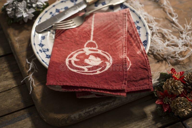 Paires de serviettes pliées par rouge de plat avec le décor de Noël images stock