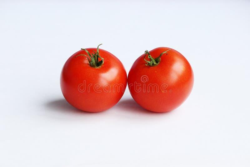 paires de tomates rouges avec les queues vertes sur une serre chaude faite maison de fond blanc images stock