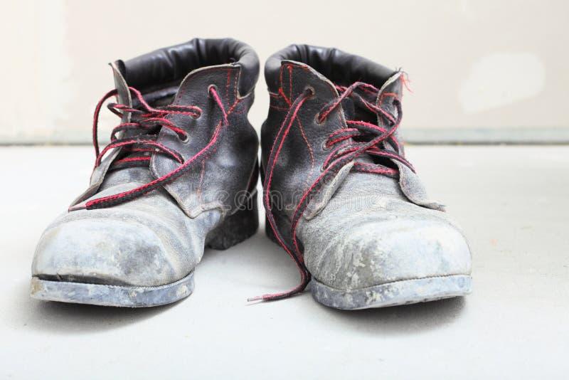 Paires de vieilles bottes de sale travail dans le chantier photos stock