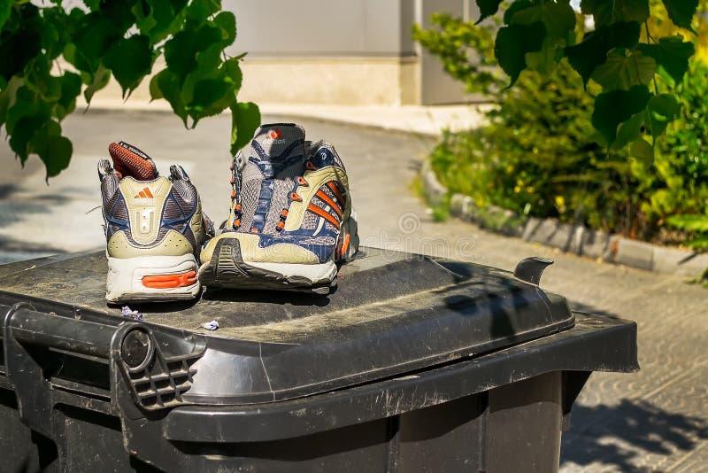 Paires de vieilles espadrilles d'Adidas en bon état sur le couvercle de la poubelle près du bâtiment résidentiel Vieilles chaussu photographie stock libre de droits