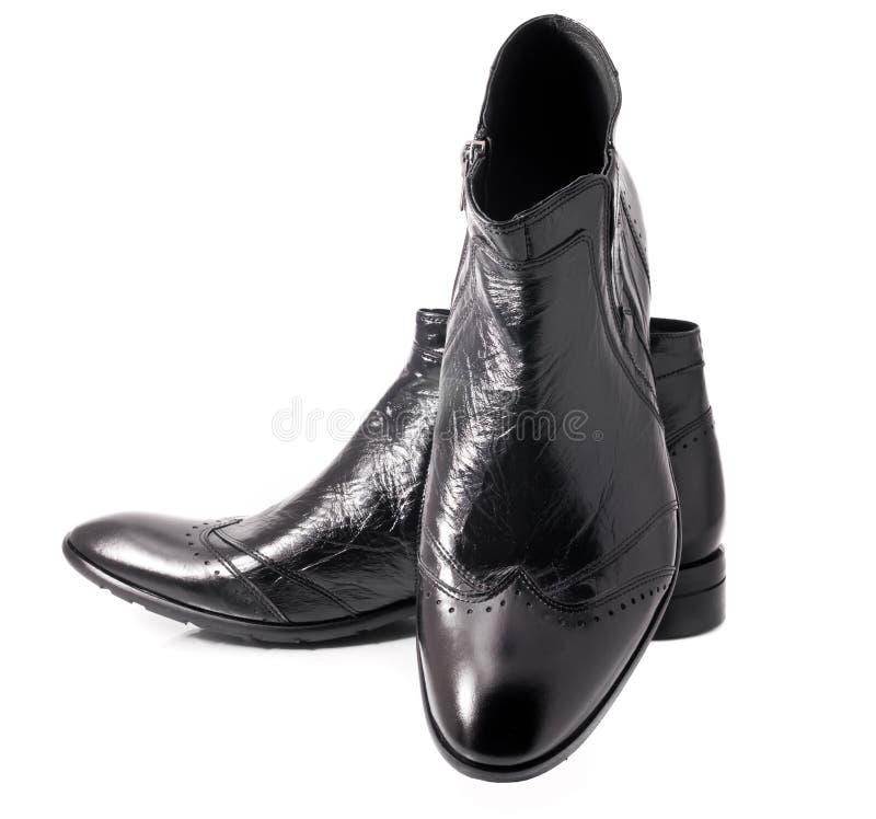 Paires des bottes des hommes en cuir noirs sur le blanc photographie stock libre de droits
