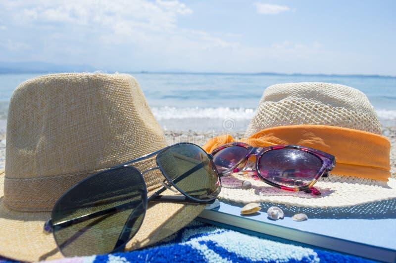 Paires des chapeaux de paille, des lunettes de soleil et d'un livre sur la plage avec la mer photographie stock libre de droits