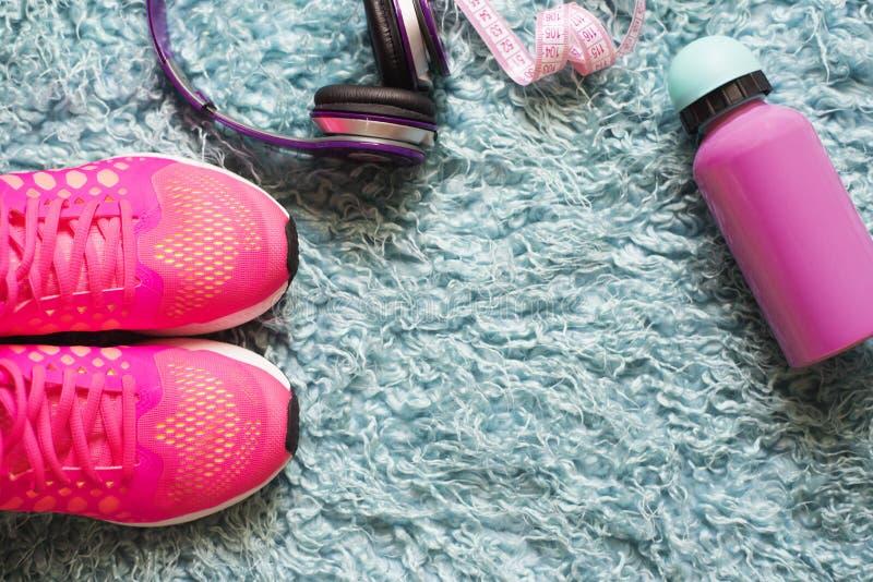 Paires des chaussures, du mètre, de la bouteille d'eau et de l'écouteur roses de sport au-dessus du tapis de fourrure À l'arrière photo libre de droits