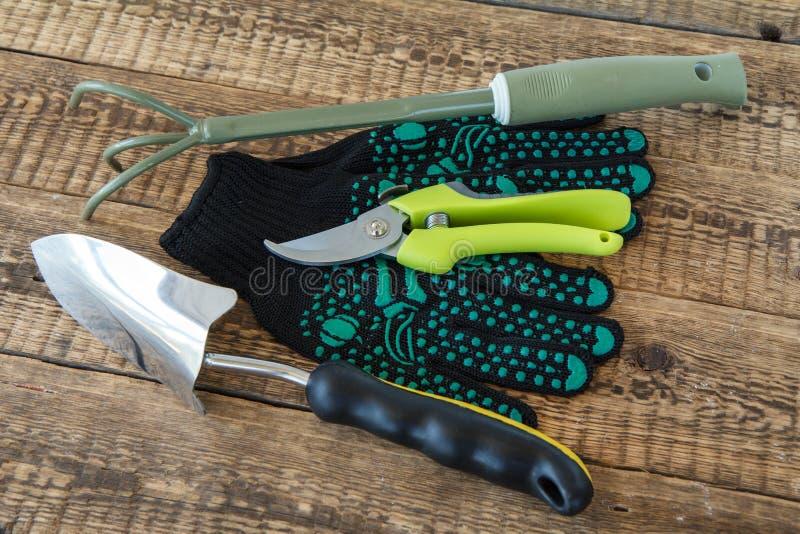 Paires des gants de jardin, du râteau de jardin de main, du pruner et de la truelle sur les conseils en bois photos stock