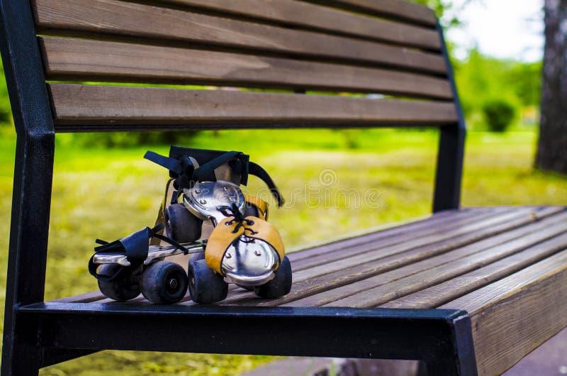 Paires du vieux patin de rouleau accrochant sur le banc Sport pendant toutes les fois photo stock