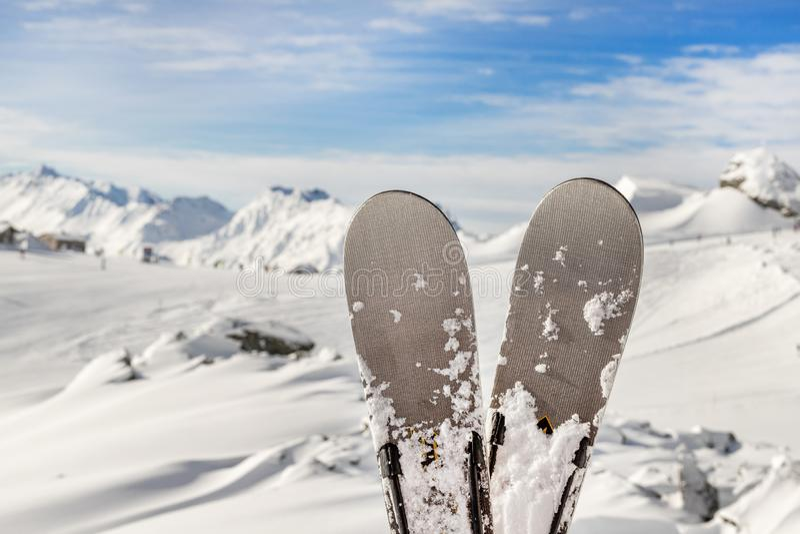 Paires en gros plan de skis sur la station de vacances d'hiver de montagne avec la vue sc?nique panoramique de t?l?ski et de bell image stock