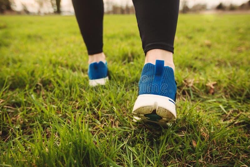 Paires sportives de jambes fonctionnant sur l'herbe photo libre de droits