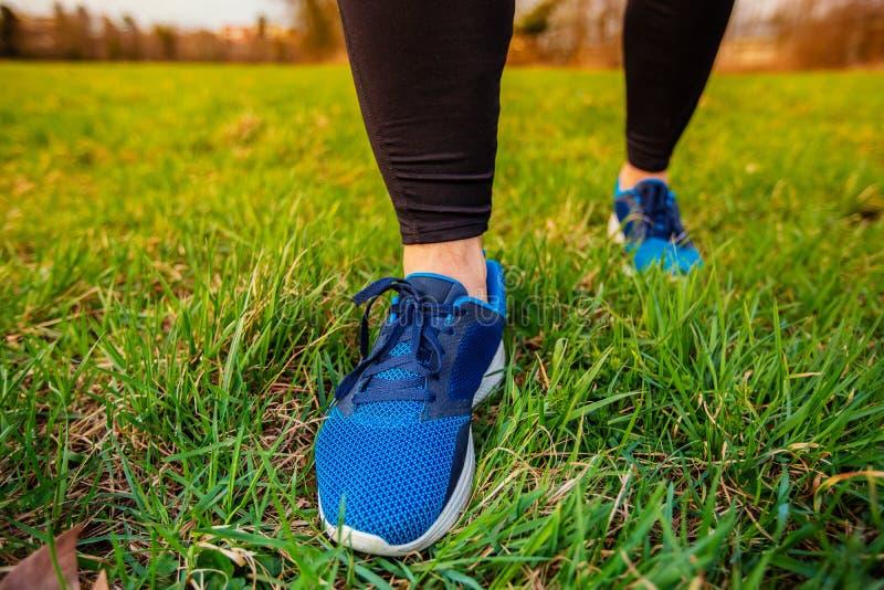 Paires sportives de jambes fonctionnant sur l'herbe photographie stock