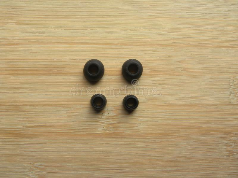 2 pairs of earphone pads. 2 pairs of different size black color earphone pads kept on wooden table stock photos