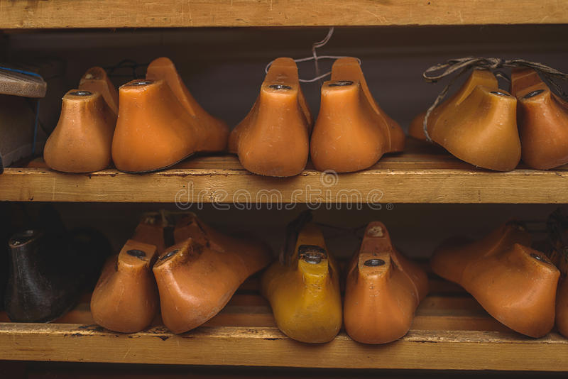 Pairs of plastic last shoes. Orange plastic shoe form lying on a rack, front view stock photos