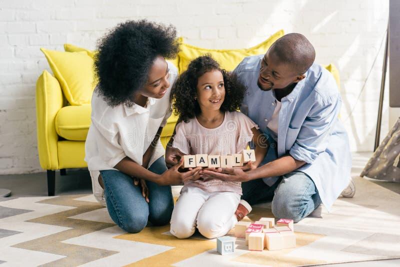 pais afro-americanos e filha que guardam blocos de madeira com a família que rotula junto no assoalho fotografia de stock royalty free