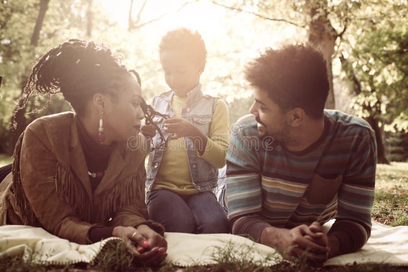 Pais afro-americanos que encontram-se para baixo na natureza e no talkin imagem de stock royalty free