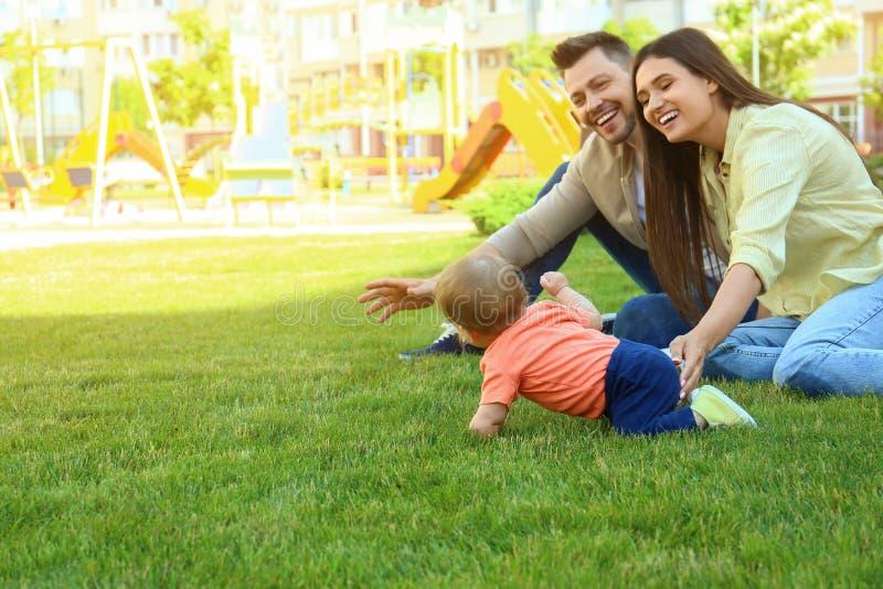 Pais ajudando seu adorável bebê a rastejar Espaço para texto imagens de stock