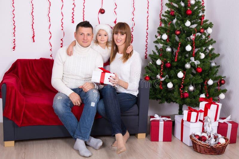 Pais alegres com a filha que senta-se perto da árvore de Natal em ho imagens de stock royalty free