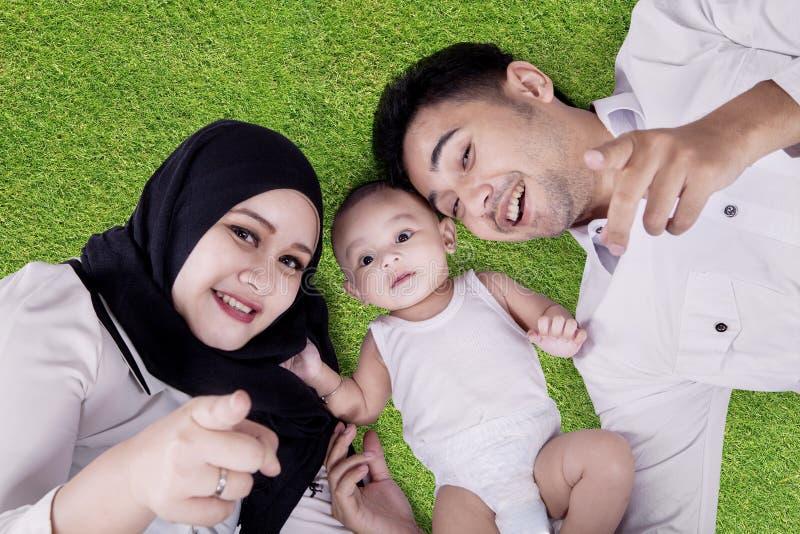 Pais alegres e bebê bonito que encontram-se na grama foto de stock royalty free