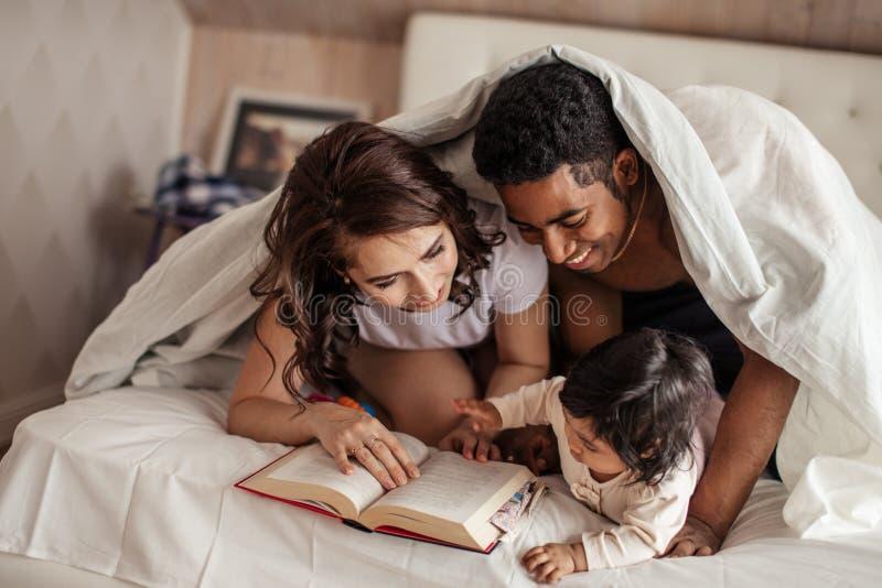 Pais alegres que leem as caudas feericamente a um bebê antes do sono da noite imagens de stock royalty free