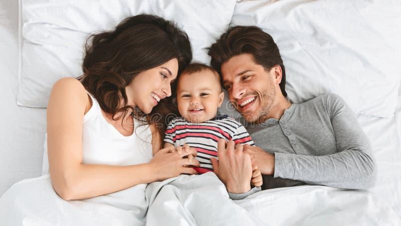 Pais alegres que têm o divertimento com seu bebê na cama imagem de stock royalty free