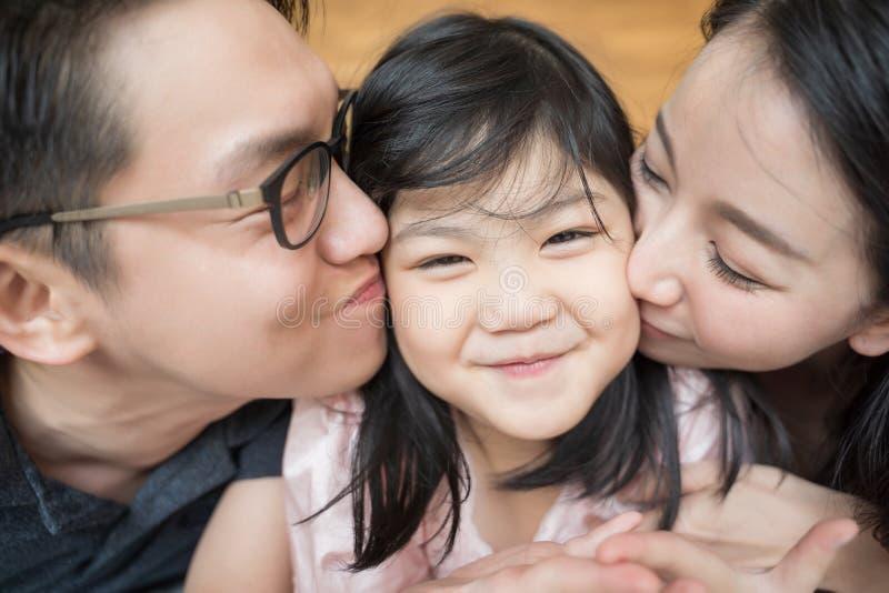 Pais asi?ticos que beijam sua pouca filha em ambos os mordentes Retrato da fam?lia foto de stock