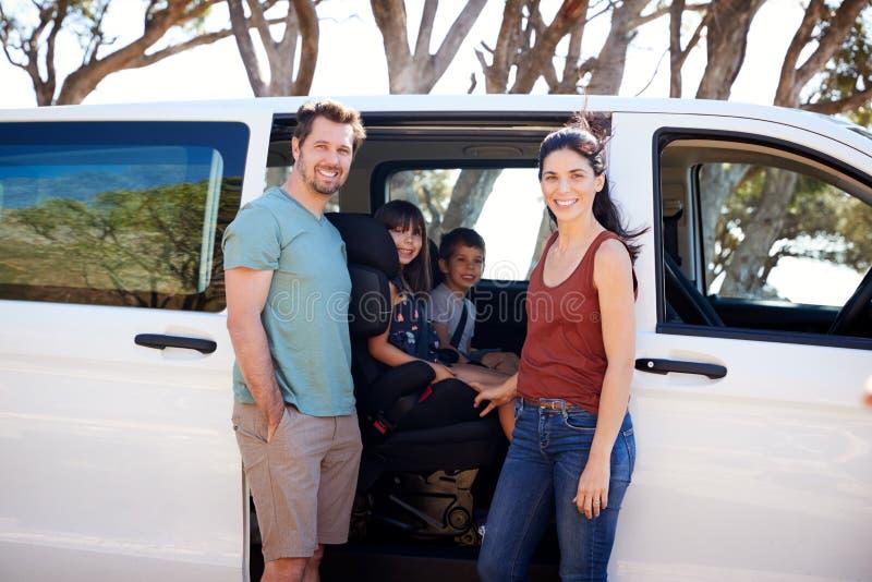 Pais brancos adultos meados de que estão ao lado do carro, suas duas crianças dentro do sorriso à câmera foto de stock royalty free