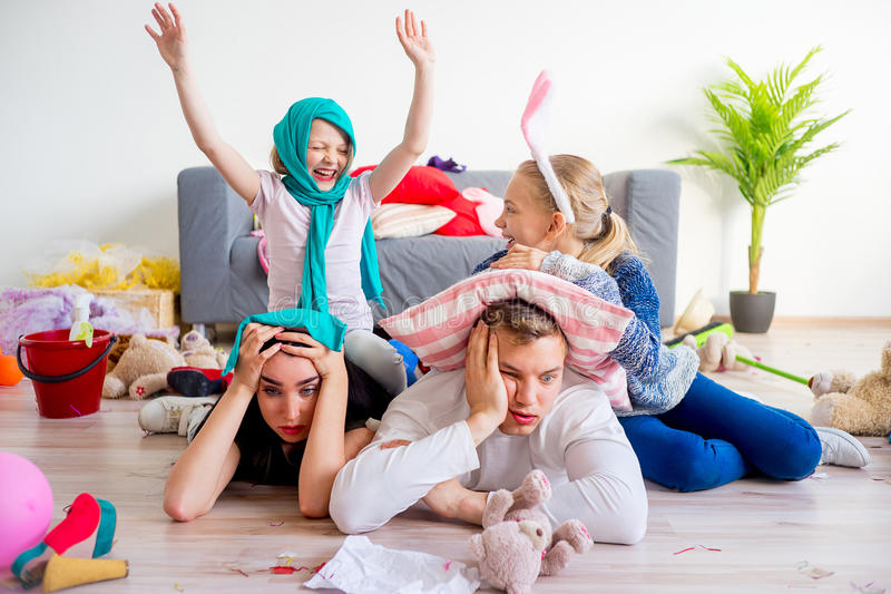 Pais cansados e crianças brincando imagem de stock royalty free