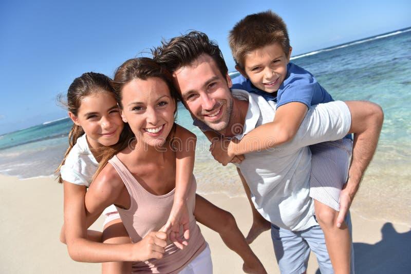 Pais com as crianças em sua parte traseira na praia imagens de stock