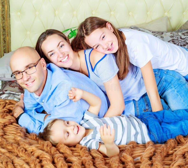 Pais com as crianças na cama imagens de stock