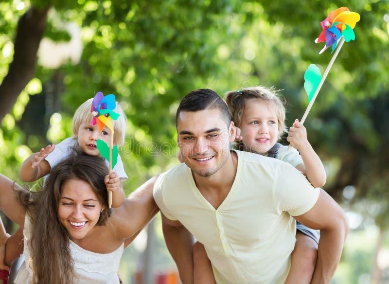 Pais com as crianças que jogam moinhos de vento coloridos imagem de stock royalty free