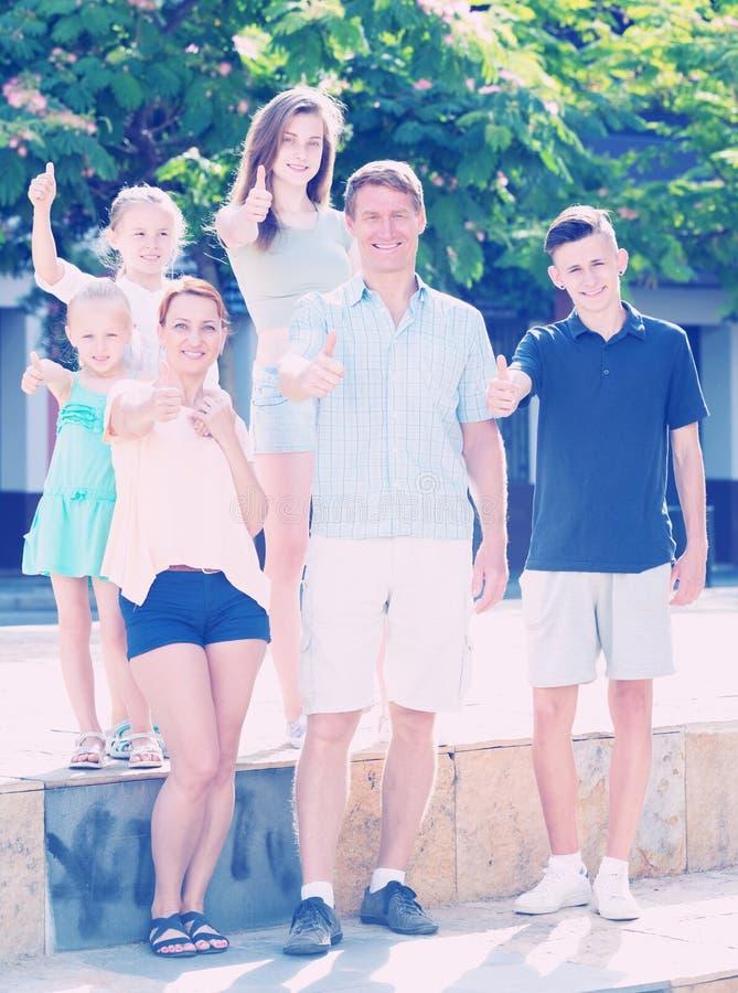 Pais com as crianças que mostram os polegares acima fotos de stock royalty free