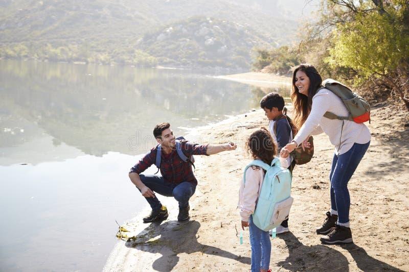 Pais com as jovens crianças que exploram ao lado de um lago da montanha fotos de stock