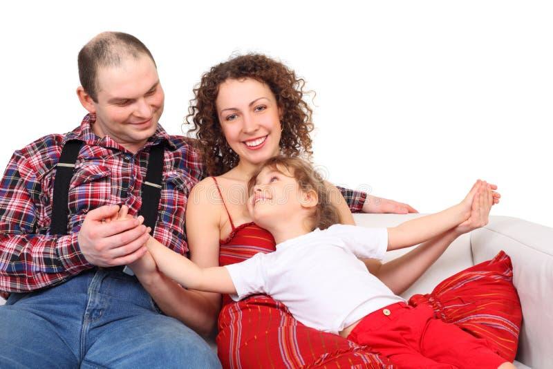 Pais com a filha no sofá do couro branco fotos de stock
